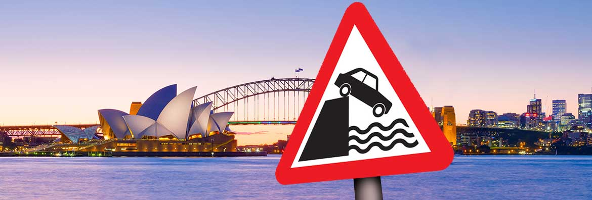 Sydney harbour with a water's edge warning sign