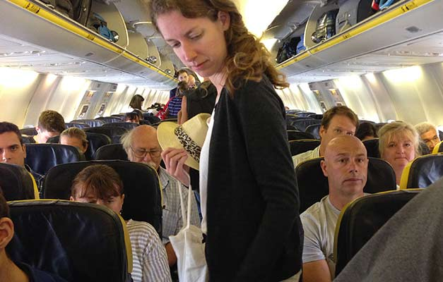 A passenger making her way to her seat during the boarding of a Ryanair flight at Jerez Airport in Spain