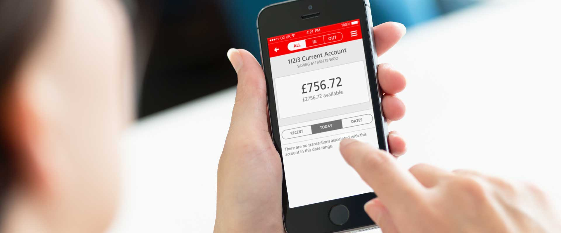 picture of a woman holding an iphone with the santander mobile banking app on the screen